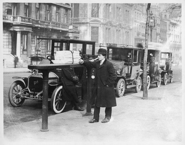 A smart Edwardian gentleman in a topcoat and bowler hat rests a heavy parcel on the taxi rank, waiting for his cab at Piccadilly, central London