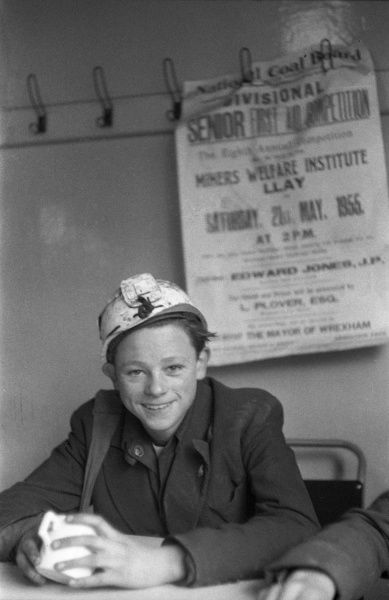 Mining Technical Institute, Burnley, Lancashire, England. A smiling young boy in a hard hat, finishes a mug of tea before returning to class. Behind him, a notice from the National Coal Board hangs off of the coat pegs