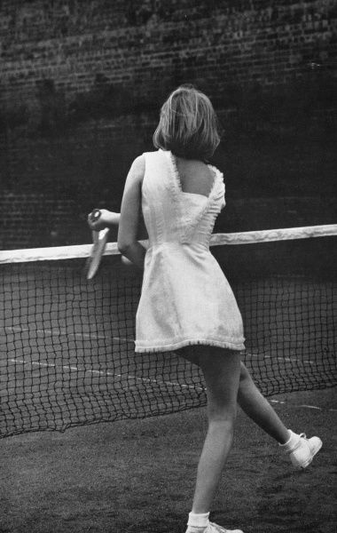 A terylene and cotton tennis dress designed by tennis fashion guru Teddy Tinling with frills trimming the hem and high neckline while the back swoops to a low and glamorous exit view. Date: 1962