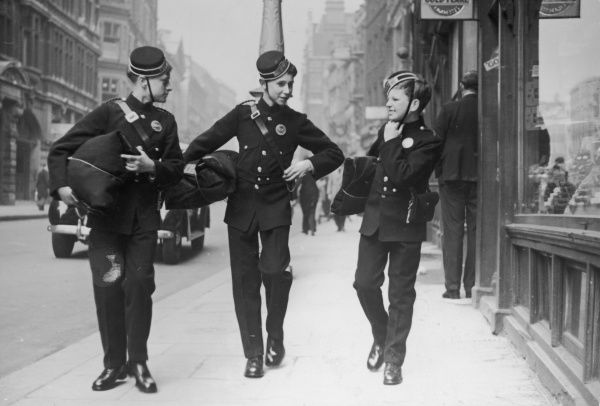 Three smart telegram boys, happy in their work, on duty on the streets of London
