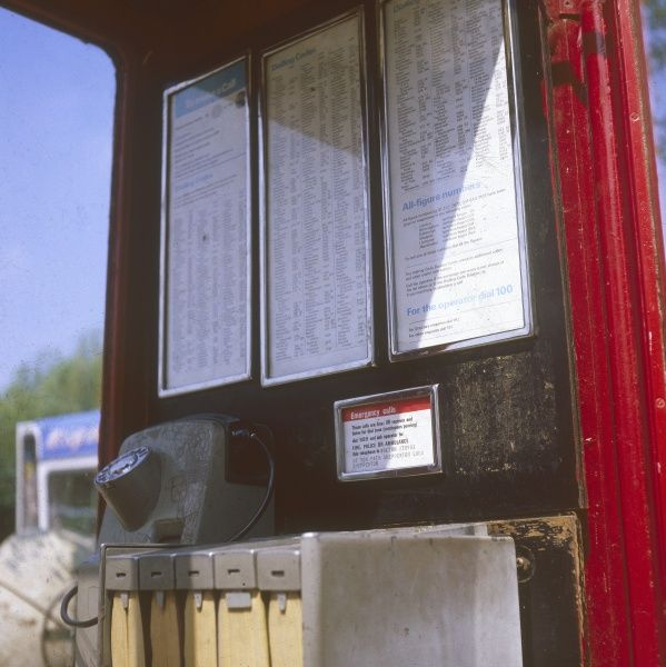 The interior of a telephone kiosk or telephone 'box', showing the pay phone itself and the telephone directories beside it. Date: 1979