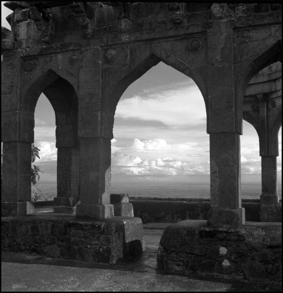 A wonderful photograph of a Temple in Mandu, Madhya Pradesh Province, India. The distinctive pointed arches frame the late afternoon light creating beauty in design and form. Photograph by Ralph Ponsonby Watts