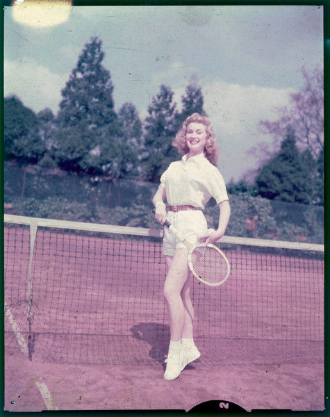 An athletic, glamorous blonde in pristine 'whites' (shorts, blouse, plimsolls, bobby socks & red belt), wooden racquet & with fuzzy balls in hand, stands on tip-toe at the net