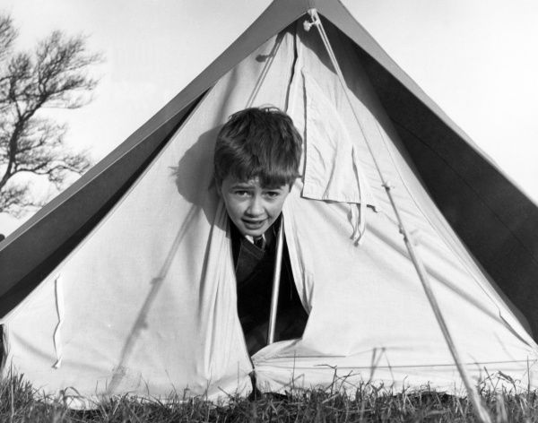 A little boy peeping out of a tent! Date: 1960s