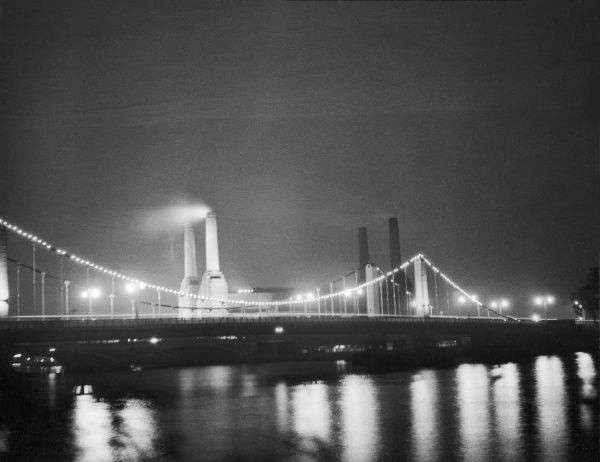 A night scene on the Thames showing Battersea power station and the bridge