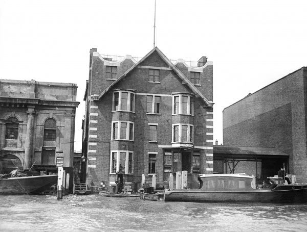 The police station for the Thames River Police, London, with a Patrol Boat moored beside it