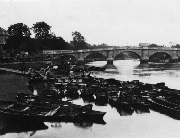 Empty punts on the banks of the River Thames, London, England. Date: early 1930s