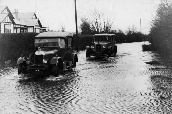 Cars making slow progress through the flooded roads near Chertsey, Surrey, England. The roads in the low-lying districts of the Thames Valley were flooded due to storms. Date: 12 December 1929