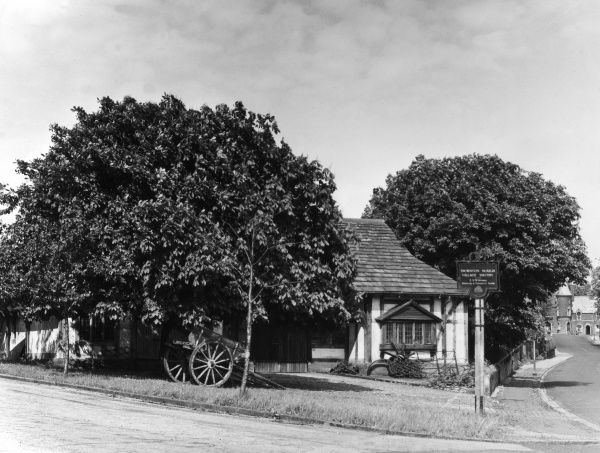 The Village Smithy (blacksmith), with its spreading old chestnut tree, at Thornton Hough, Wirral, England. Date: 1950s