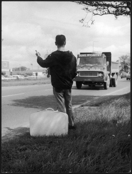 A young man hitch hiker, thumbs a lift from a Denis McCarthy lorry