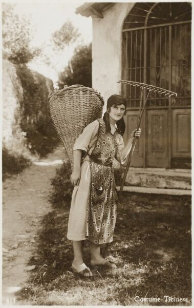 A Ticino Woman - Switzerland in traditional costume, holding a wooden rake with a large woven reed basket on her back