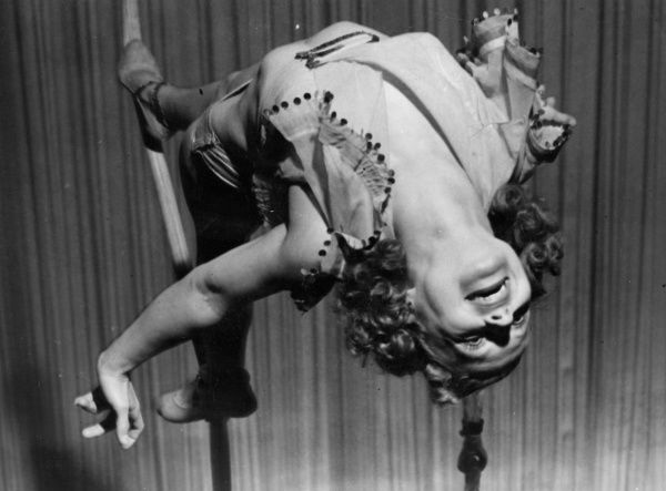 Standing on a horizontal rope is not unduly easy, but female tightrope artiste 'Mickey' stands on a vertical one and makes it look like a walk in the park! Date: 1940s