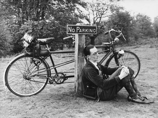 A tired cyclist rests against a signpost, with his tandem leaning close by