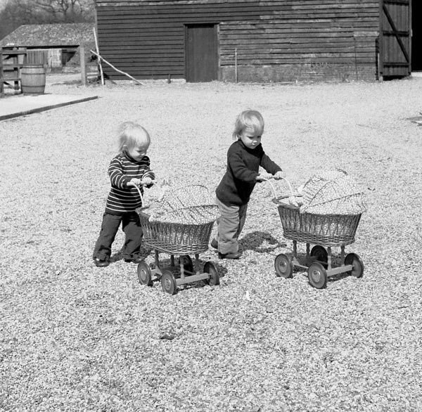 Two toddlers wheeling carry cots across a stretch of gravel
