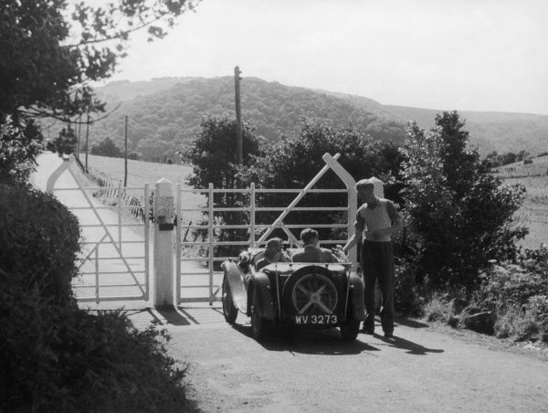 A young couple in an open-top sports car pay their dues at the Woody Bay toll gate at the beginning of the private road from the Valley of the Rocks to Martinhoe Church, Devon