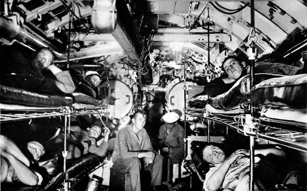 Photograph showing the crew of a German submarine (U-boat) relaxing in their bunks in the bow torpedo chamber, c.1938. This photograph shows the cramped conditions typically of the submarines that served in the Second World War