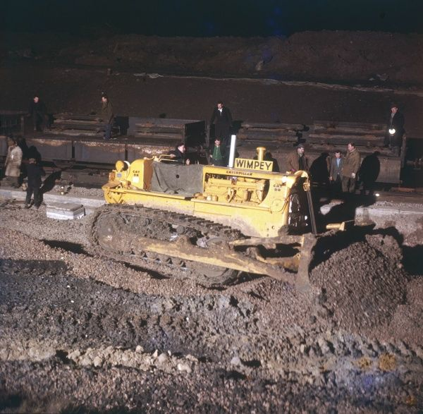 A Caterpillar bulldozer being operated during track laying by the Wimpey construction company. Nightime engineering works. Photograph by Heinz Zinram