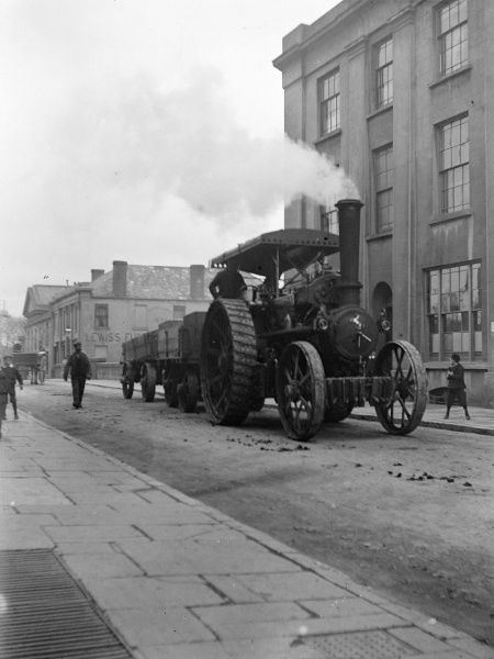 A large traction engine with a smoking funnel transports a load of stone from the station, along Victoria Place, Haverfordwest, Pembrokeshire, Dyfed, South Wales