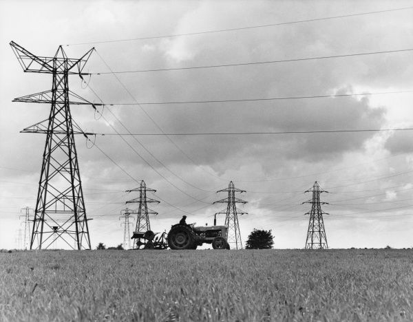 A tractor ploughing over autumn stubble beneath ominous electricity grid pylons on a farm in Suffolk, England