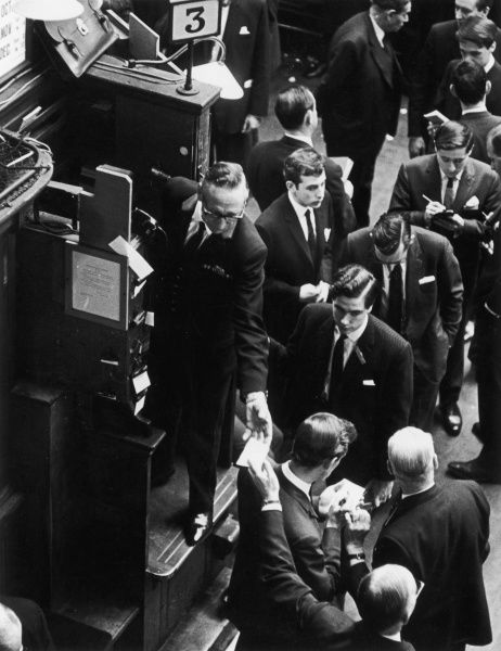 A trader passes a note from the exchange floor to a colleague in a booth, who will deliver the information on the deal
