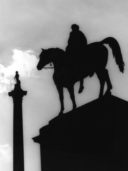 Silhouettes in Trafalgar Square, London. The equine statue in the foreground is George IV, with Nelson's Column in the background. Date: 1950s