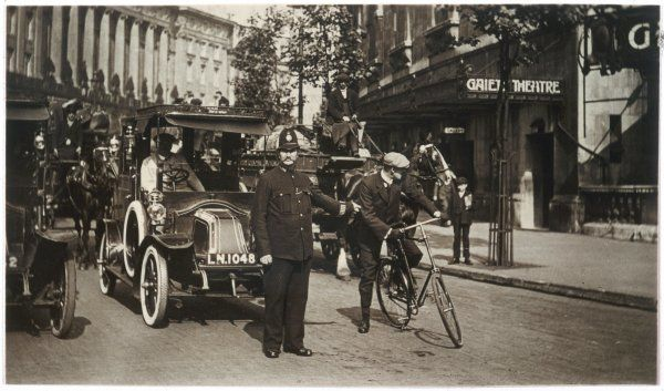 A policeman controls the traffic in London. Here he holds up a car, a horse and cart and a bicycle