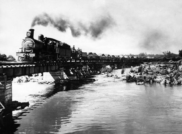 A train pulling loaded trucks across the Orange River in South Africa during the First World War. The driver and his mate are standing by the engine, and a group of British soldiers are standing further back -- all are looking towards the camera