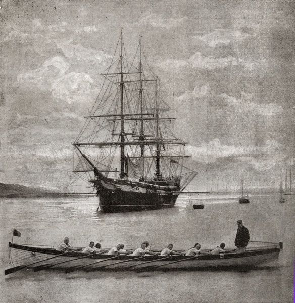 The racing crew of the training ship Mercury with the ship itself in the background. The Mercury, established in 1885 by Charles Hoare, was originally based at Binstead, Isle of Wight, but moved in 1892 to the River Hamble, near Southampton, Hampshire