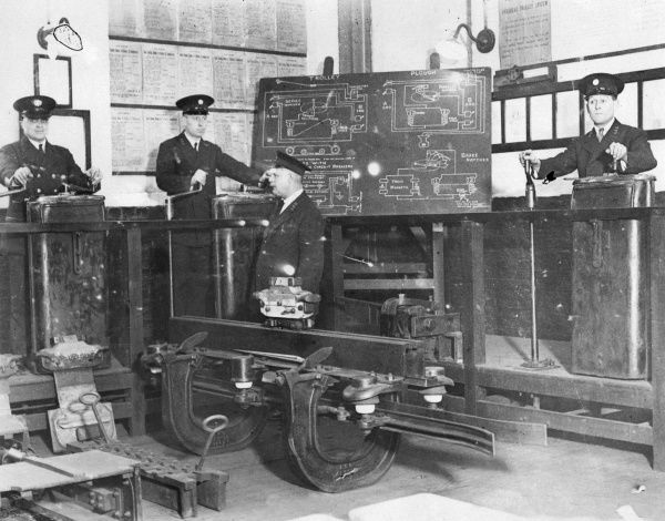 A tram driver receiving instruction in the handling of (dummy) controls at the Clapham Depot of the London County Council School for Tram Drivers. Date: 1930s