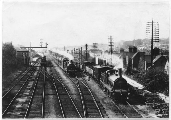 A goods train waits on one track to let the passenger train go through, while a third train approaches through the station at Redhill, Surrey