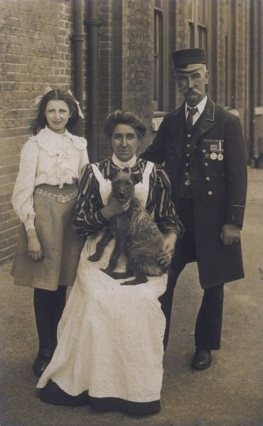 FAMILY GROUP WITH TERRIER DOG POSE FOR PHOTO IN STREET. FATHER OF FAMILY WEARING A LONDON TRAMWAYS UNIFORM
