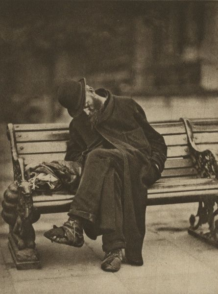 A tramp asleep on a bench on the Thames Embankment in London. He is wearing an old dressing-gown as an overcoat and his shoes are held together with string. Date: circa 1926