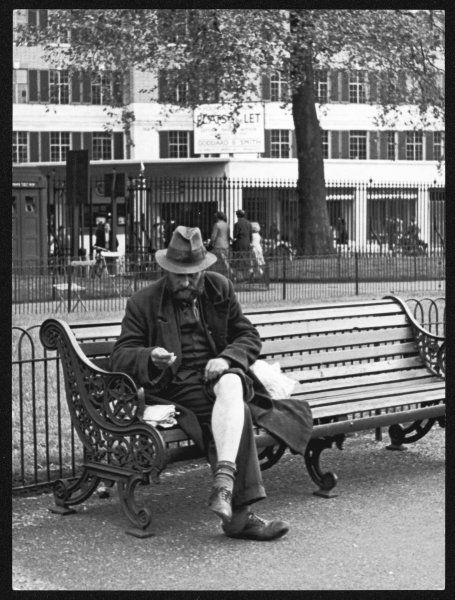 'Visible mending' - a tramp shows a bit of leg as he mends his clothes on a bench in Hyde Park, London, England