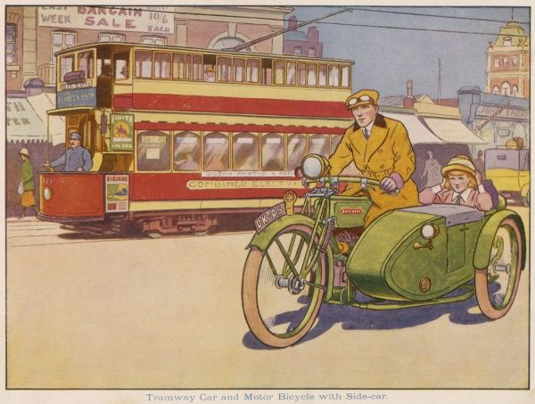 A tram car travels along its route in town while alongside, a lovely green motorcycle is driven by a man while a little girl sits primly in a side car