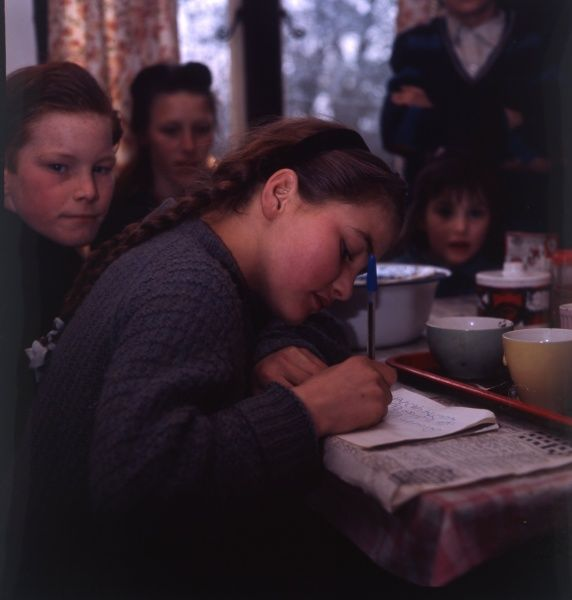 A travelling gipsy family inside the bungalow where they have been rehoused, in Beare Green, Surrey. The girl nearest the camera is writing in a notebook, perhaps to show that she is attending school and doing her homework