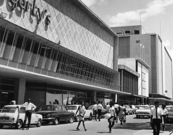 A street scene in the Port of Spain, Trinidad, West Indies, showing lots of smart workers going about their business. Date: 1960s