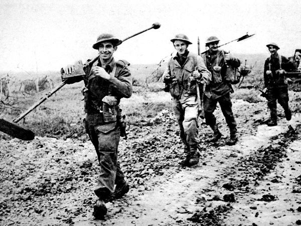 Photograph showing men of the Royal Canadian Engineers, carrying mine-detectors, moving west of Ortona, Italy, during December 1943. These men were serving with the Allied army as it pushed northwards through Italy, against Italian and German resistance