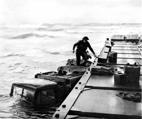 Photograph showing a three-ton truck sunk alongside a pontoon, during the Allied landings in the Nettuno-Anzio area, 1944. The rough seas, visible in the background of this photograph, were a great problem to the Allied naval operations