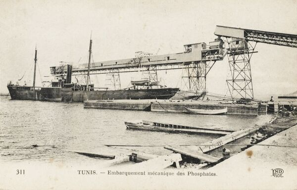 The loading of ships with Phosphates using a complex mechanical lift and harbour transport at Tunis, Tunisia