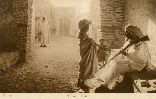 An absolutely stunning street scene in Tunisia, with a young boy talking to his seated Father, holding a rifle over his shoulder