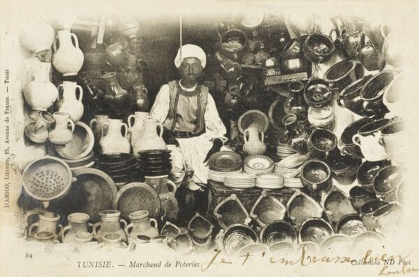 A Tunisian potter surrounded by his wares in his shop