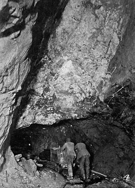 Photograph showing two miners pushing a cart of ore along a tunnel in the St. David's mine, near Carnarvon in Wales, 1911. This mine, 500 feet deep, was one of three in Wales producing gold at that time