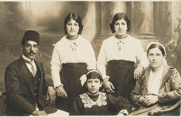 A photograph of a Turkish family group, featuring a pair of twins, standing together in identical costume. The Turkish man on the left in class period attire with a superbly neat moustache and fez hat
