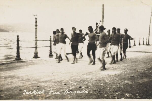 Turkish fire brigade running along the waterfront at Constantinople carrying a hand-pump