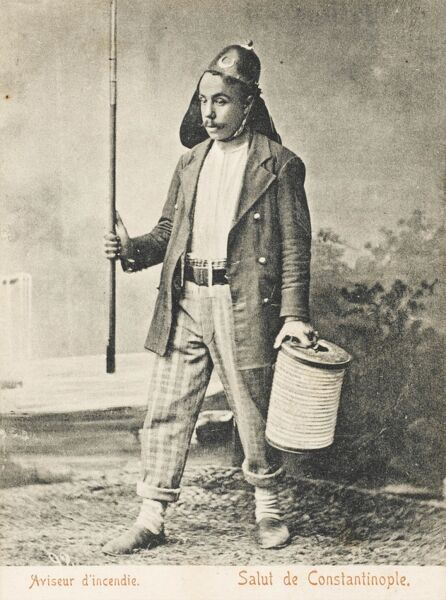 Turkish firewarden, holding a ceremonial rod in his right hand and a roll of hose in his left. Most of the houses in Constantinople were made of wood and cooking done on charcoal, so fires were very commonplace!