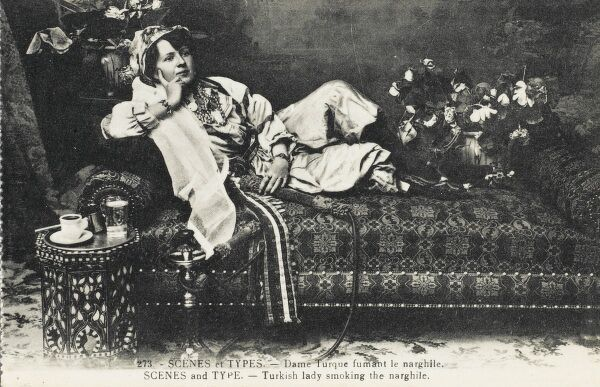 A Turkish lady reclining quizzically on an Ottoman settee, smoking a narghile pipe, whilst drinking coffee