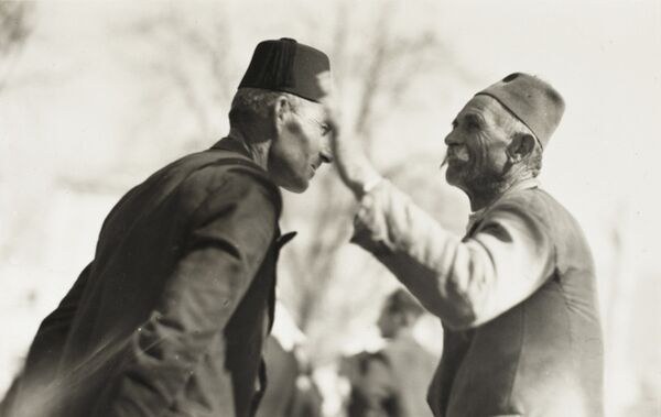 A poor elderly Turk on the right makes a point to a richer man on the left (in fez hat)