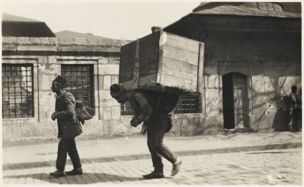 Turkish porter carrying (struggling beneath!) an enormous wooden crate up a street in Constantinople, Turkey
