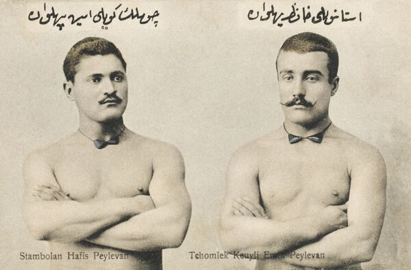 A spectacular postcard photograph of two Turkish wrestlers, showing off their muscles, finely crafted moustaches and bowties!