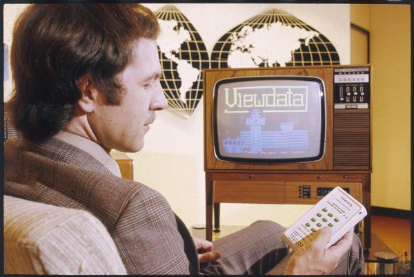 A fashionable young man in a beige jacket adjusts the text service on his television with the aid of the latest gadget - a remote control!
